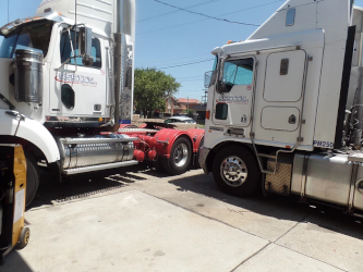 Two trucks side by side being serviced at K&C